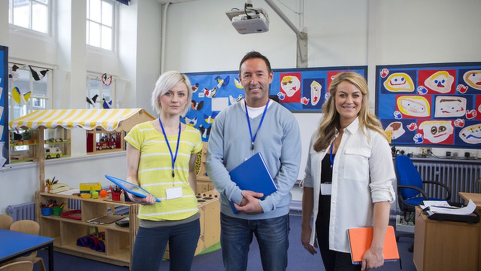 Three professors smiling standing in the middle of a classroom