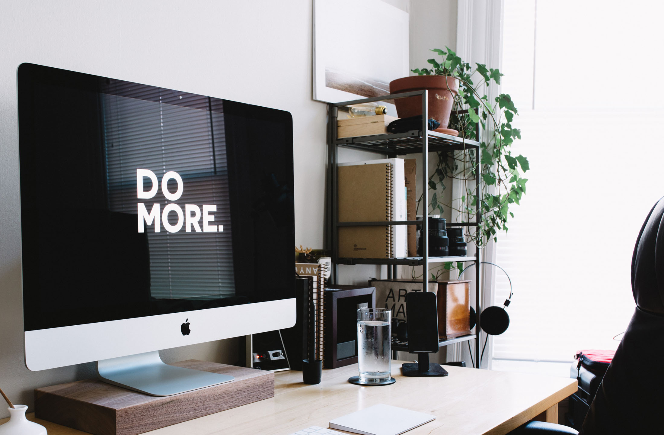 Business work from home desk computer says Do More indoor plants organized shelf