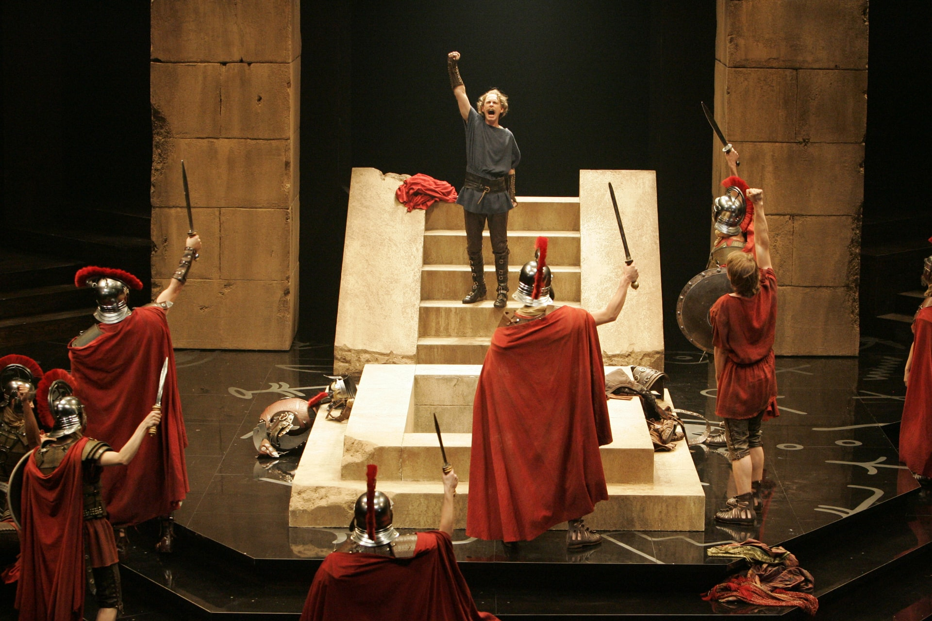 Man raises fist on stairs in from of red-cloaked Roman soldiers.
