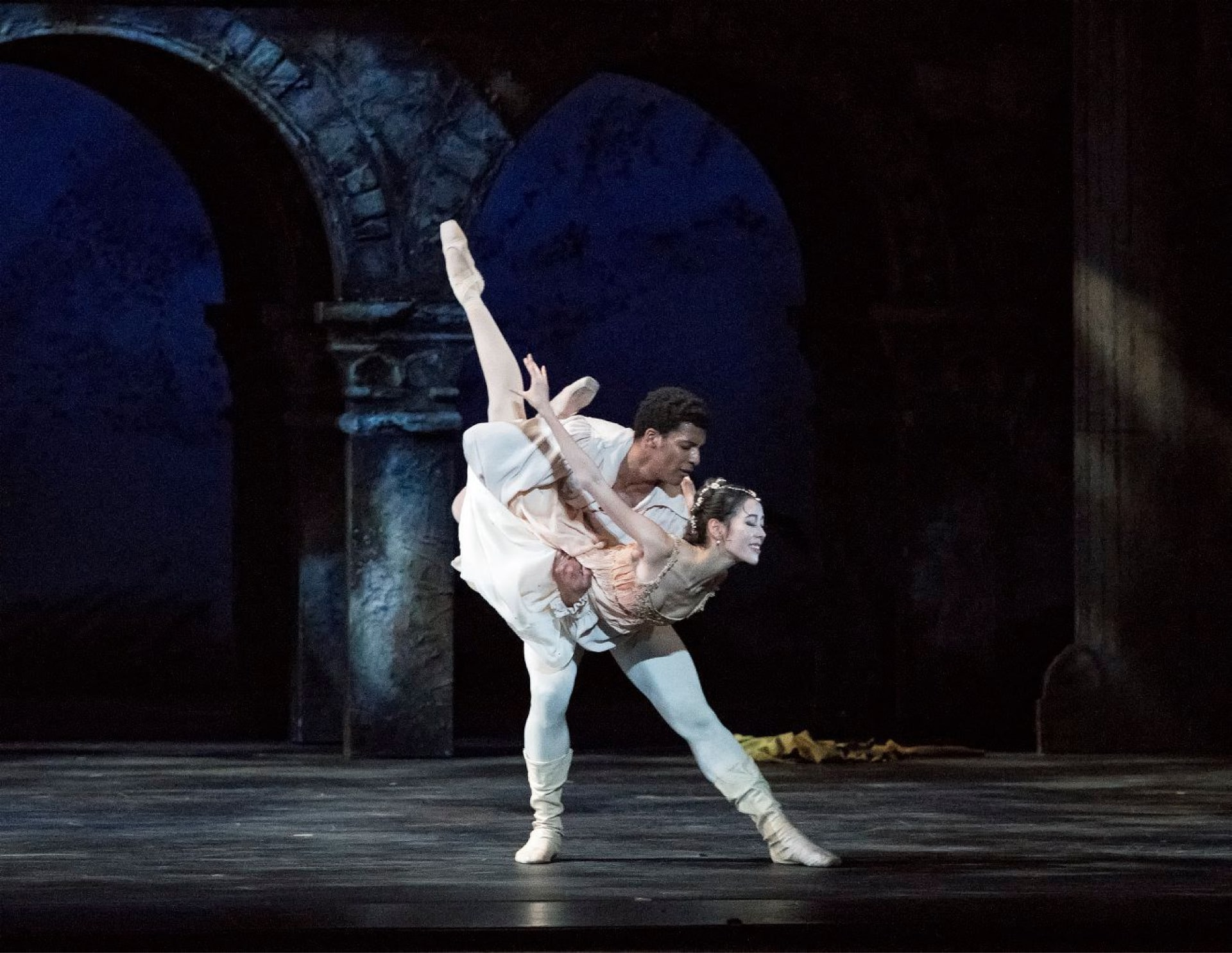 Dancer in white holds ballerina aloft on dappled stage in front of bridge arches and blue sky.