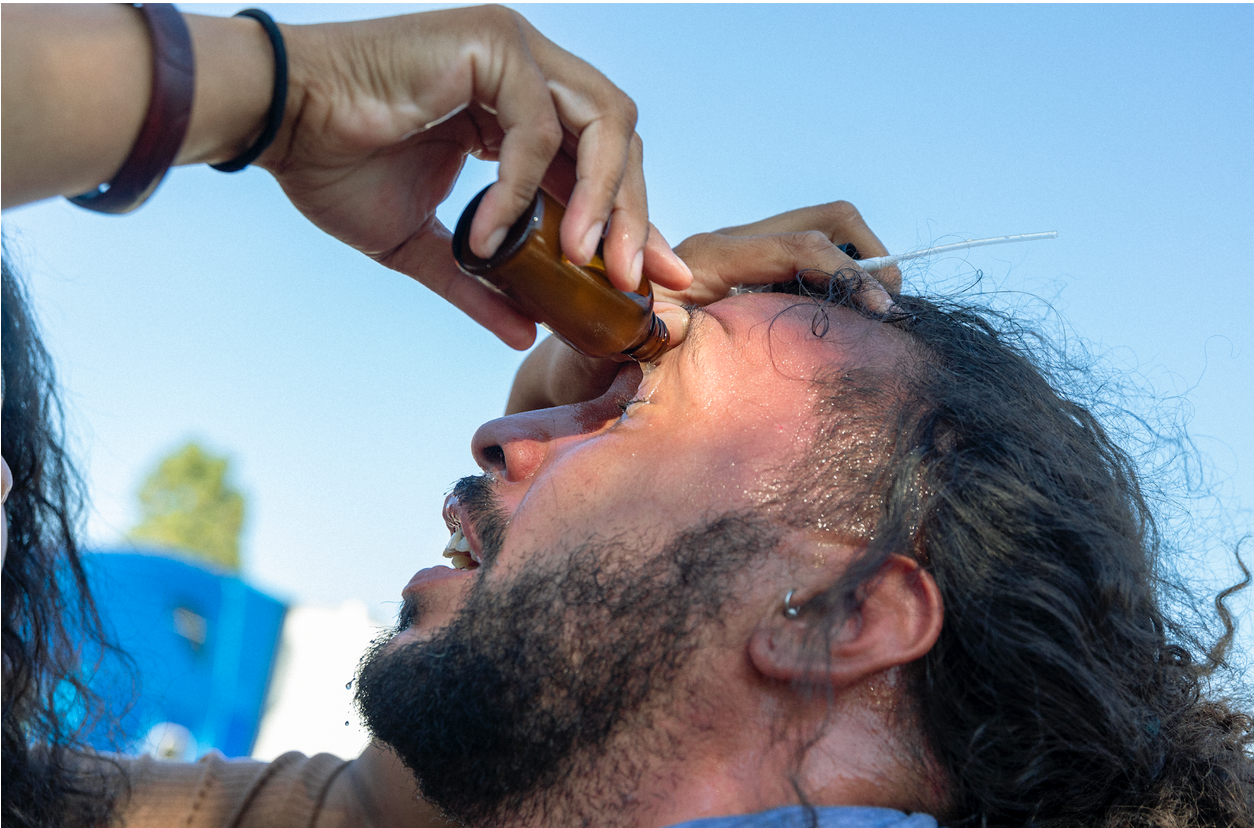 Protester washes mace from his eyes with help from a street medic.