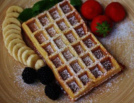 Belgische Waffel, verziert mit Puderzucker, Erdbeeren, Bananen und Brombeeren