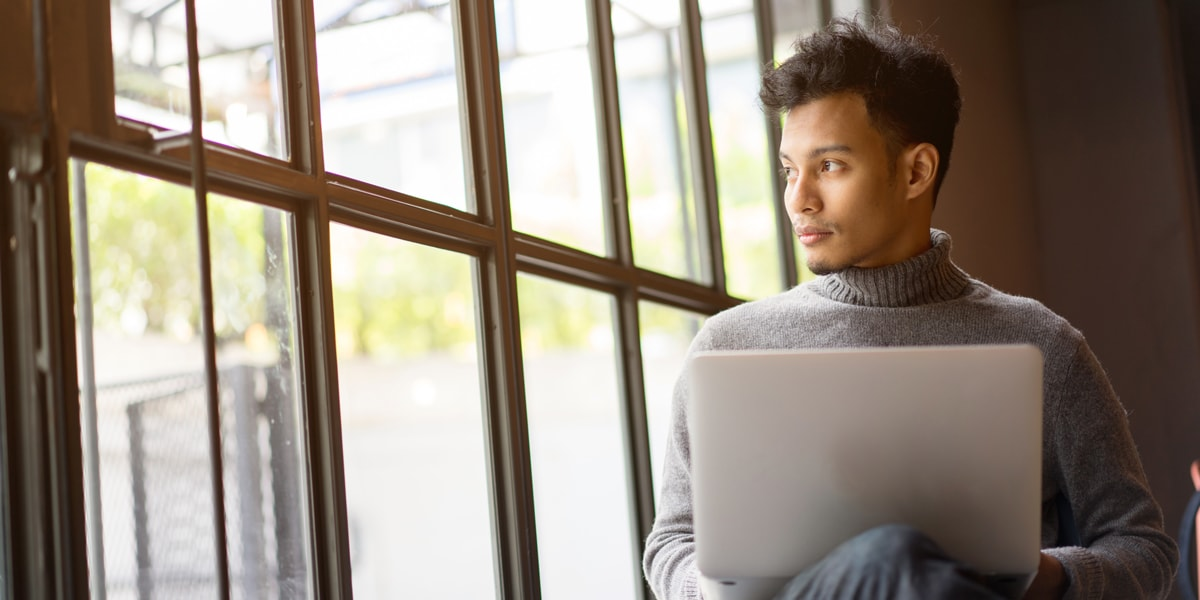 A UX designer sitting in front of a laptop, looking sideways