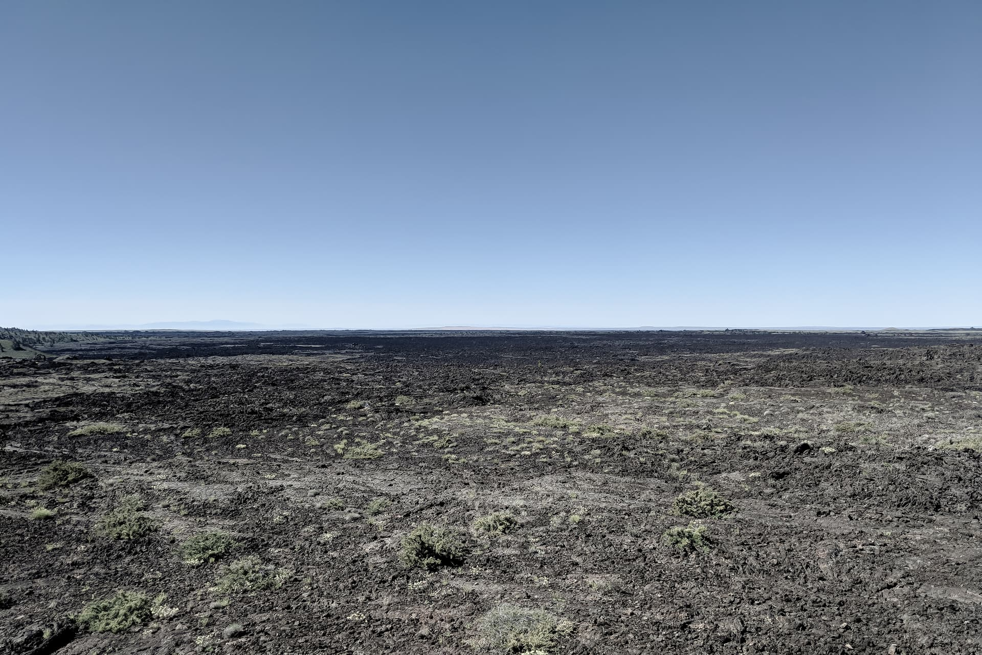 A rugged, flat, black lava flow stretches from horizon to horizon.