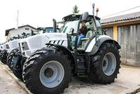 Photos of a very large tractor with a woman at the wheel