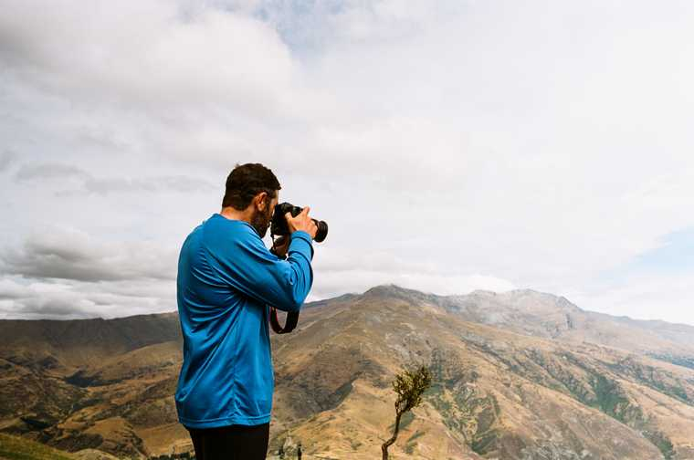 Jeb looks through the viewfinder of a DSLR camera, mountains in the distance.