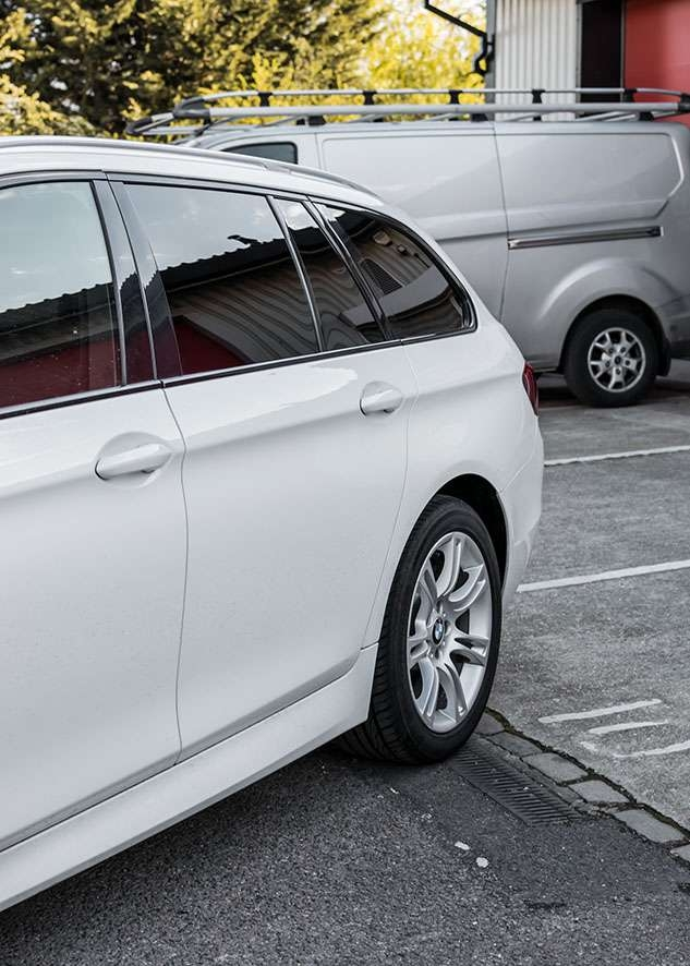 Rear side shot of white BMW 5 series with tinted windows