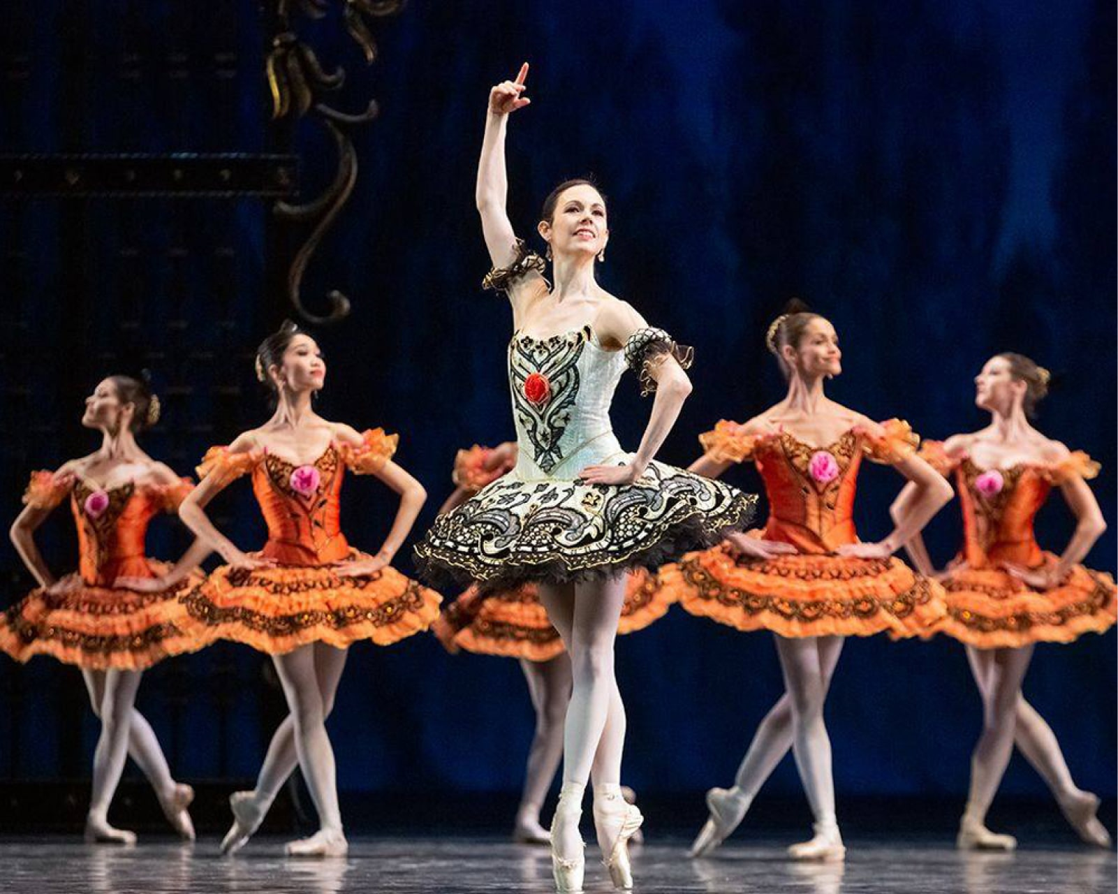 Ballerina in black and white tutu holds pose on point in front of chorus in bright orange tutus.