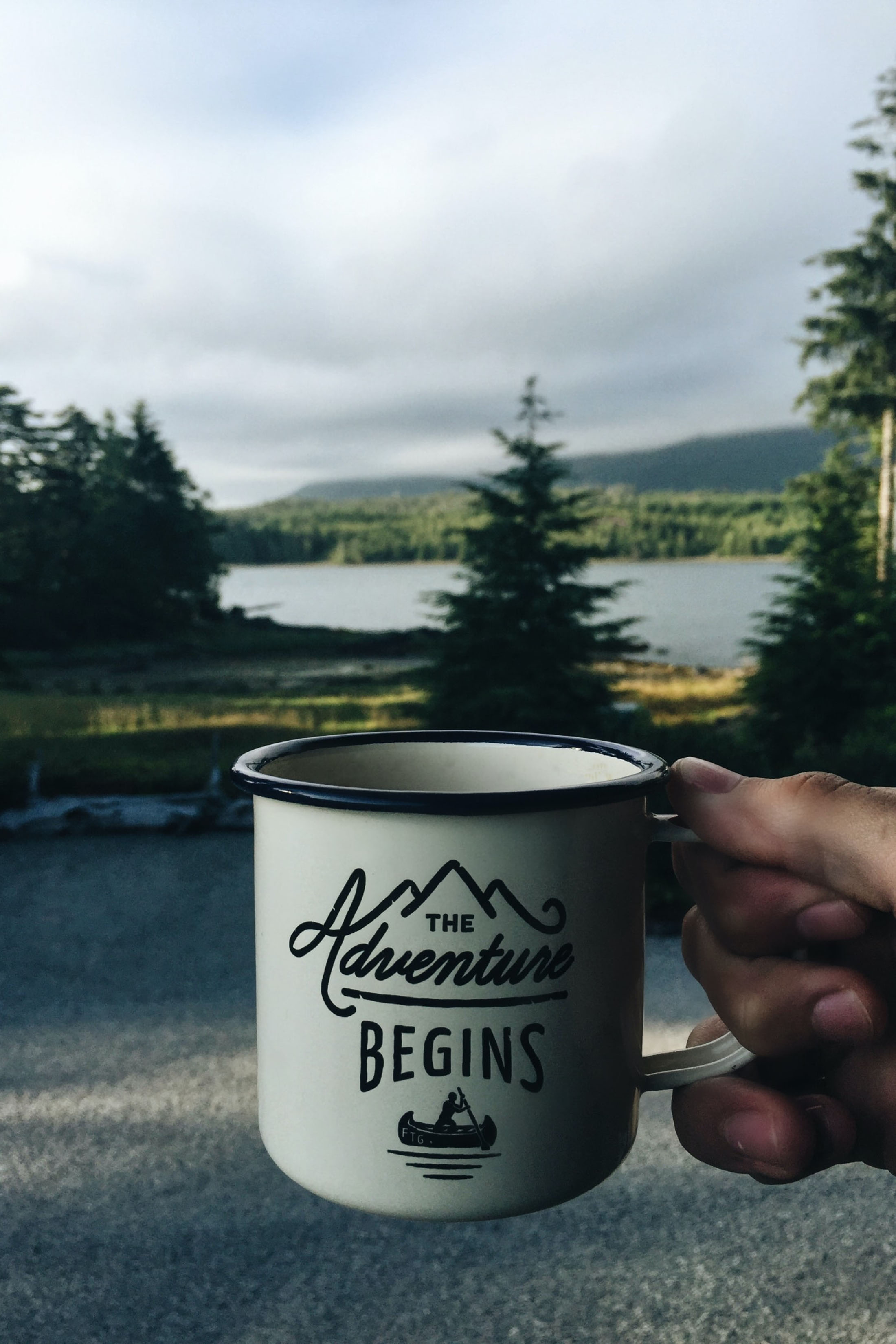 Person camper holding coffee mug that has The Adventure Begins embossed beautiful canadian forest