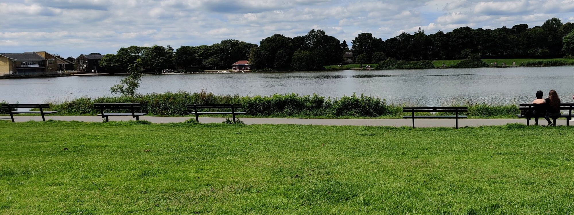 Green grass and lake in the background with trees behind. Couple sat on a bench to the right.