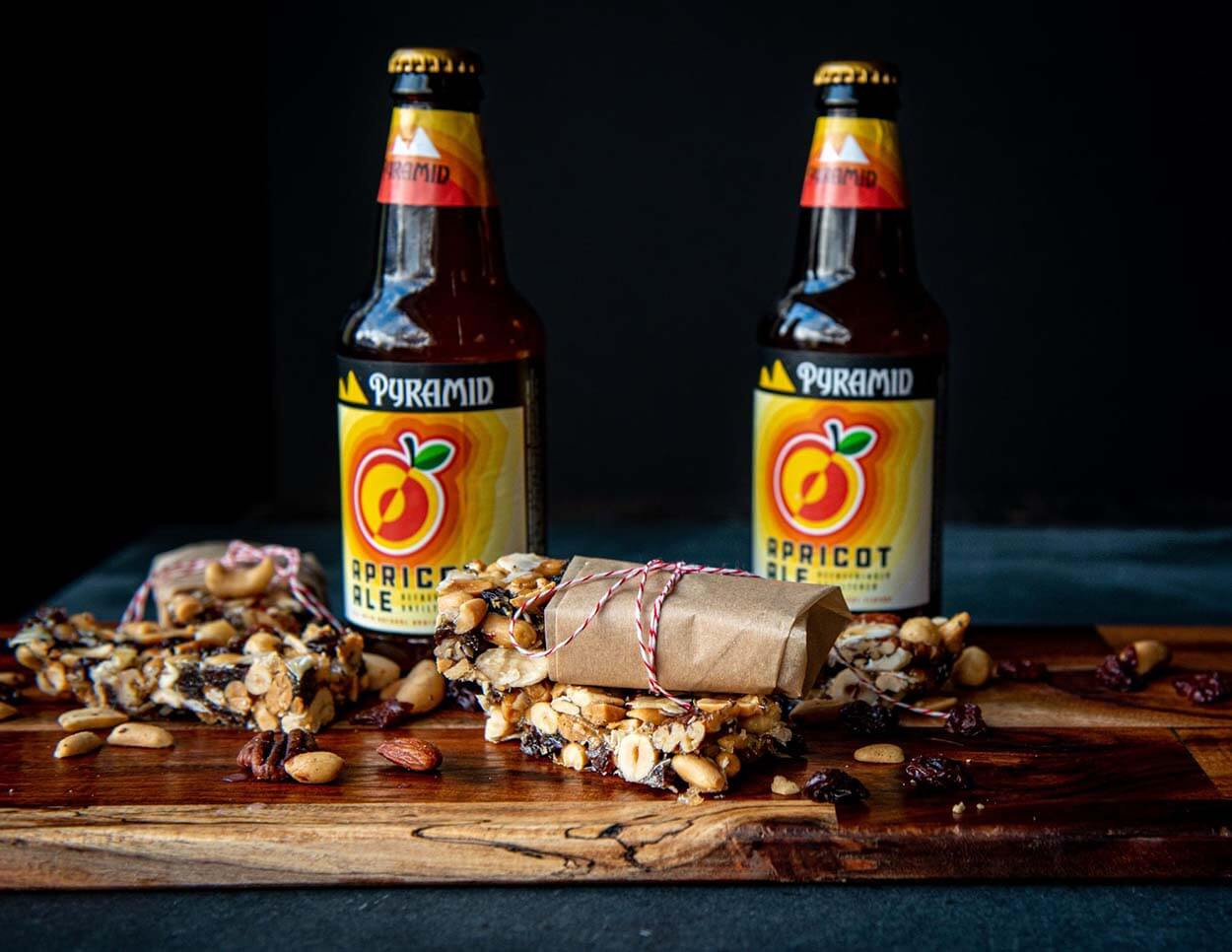 A wooden charcuterie board showing off an assortment of freshly made Apricot Ale Trail Bars along with 2 bottles of Pyramid's Apricot Ale