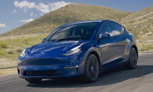 A Tesla Model Y promotional image, showing an actual Model Y driving along a deserted road (with a mountain in the background).