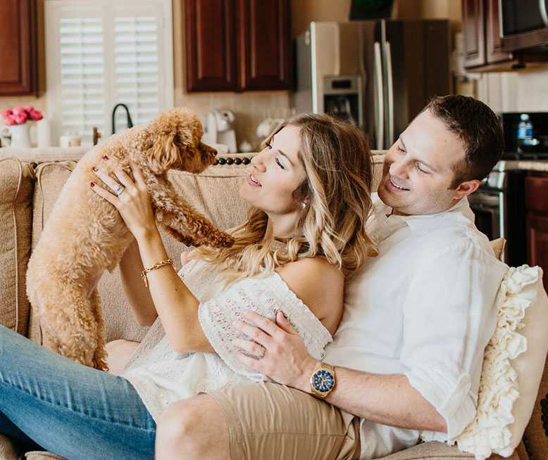Couple Sitting In The Sofa While She Plays With Her Emotional Support Dog