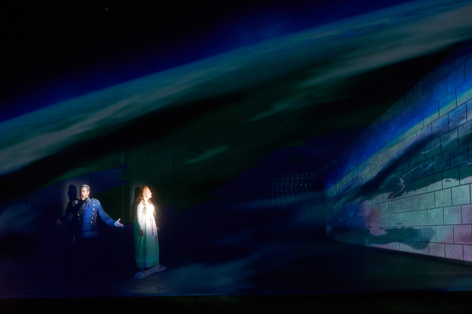 Man in blue uniform sings as bride in spotlight gazes at colourful view of earth from space.