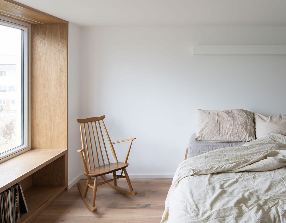 Interior view of the warm oak timber window seat in the new master bedroom suite within From Works loft conversion and rear dormer extension in Blackheath, London.
