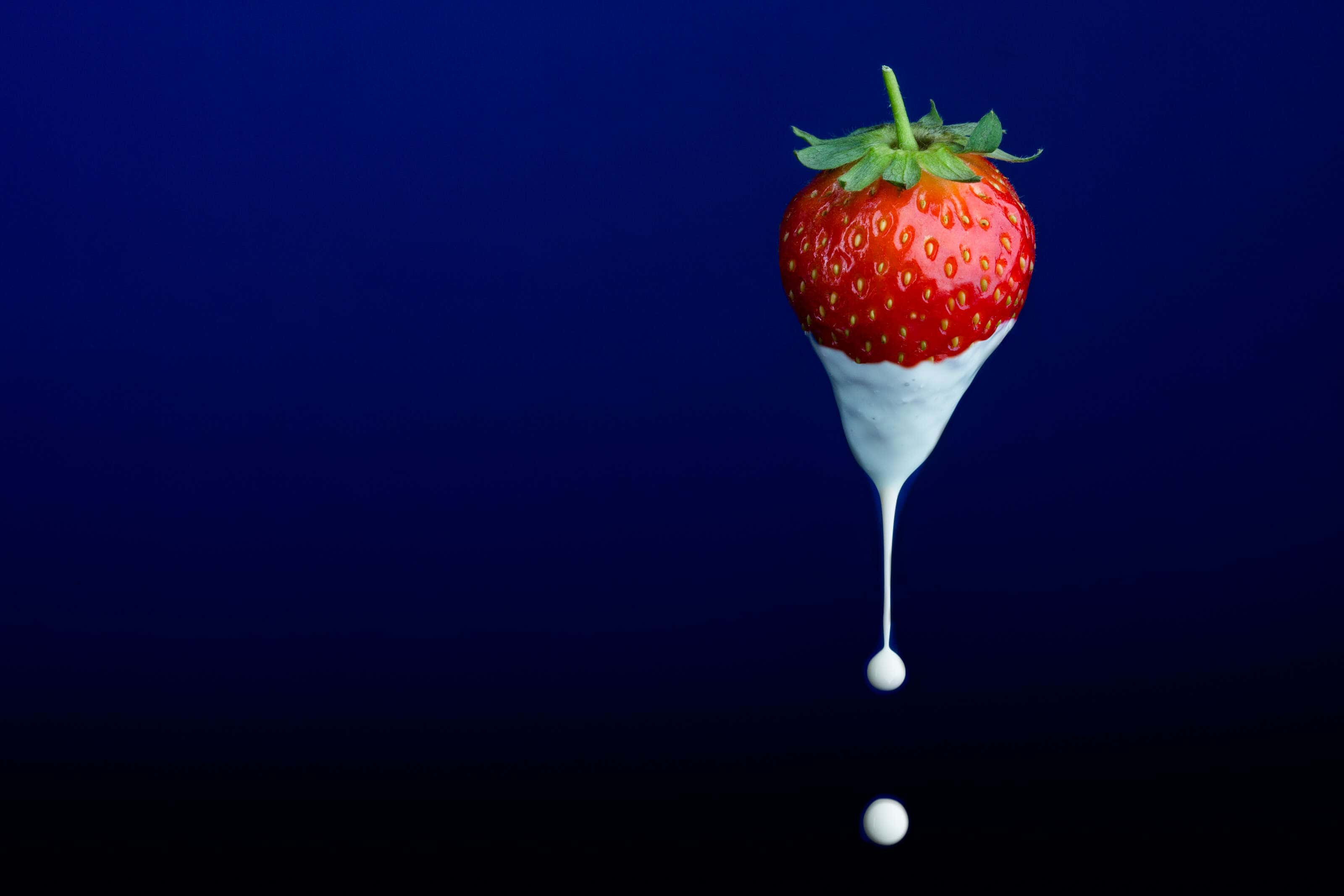a strawberry suspended mid air with a drip of cream falling off it.with a drip of cream