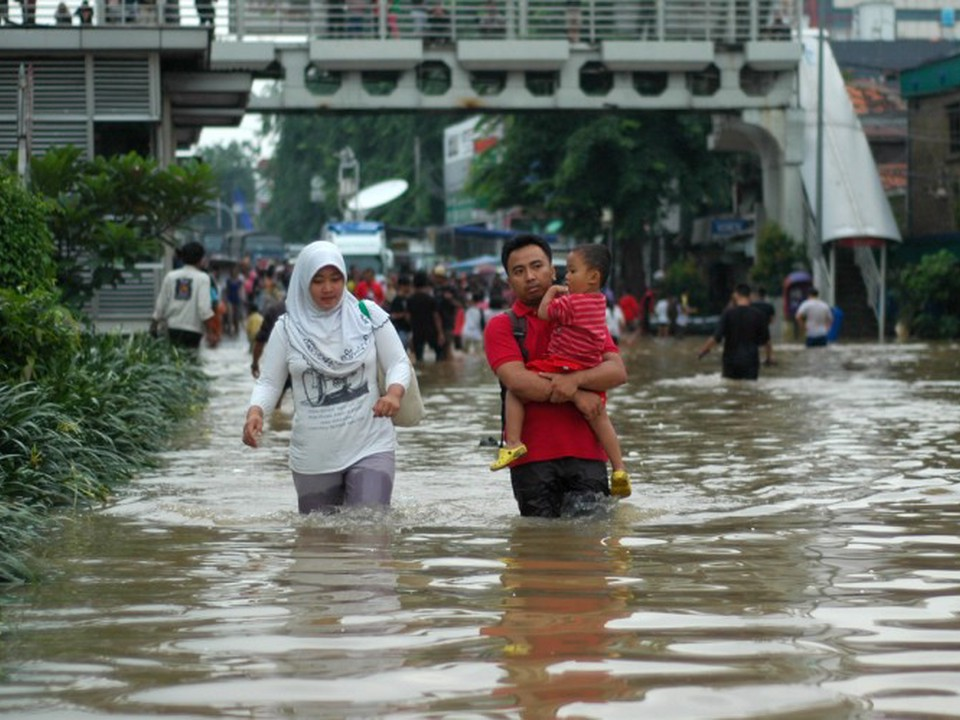 An Indonesian family wades through flood waters, part of a community that is affected by collective trauma after a natural disaster.