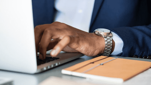 Intrapreneur businessperson types on laptop on desk next to notebook and pen #business