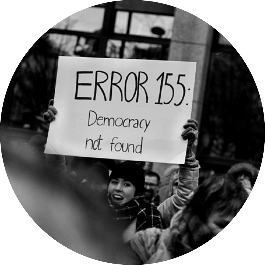 A female protestor holding up a sign saying 'Error 155: Democracy not found'..