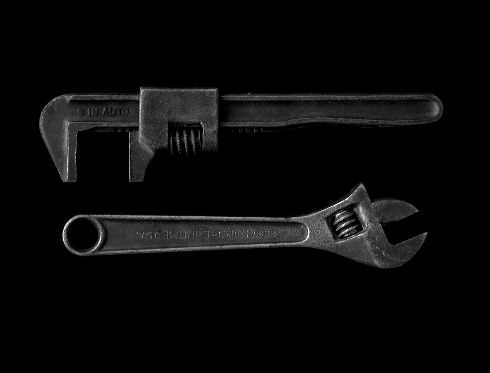 two wrenches on a black background