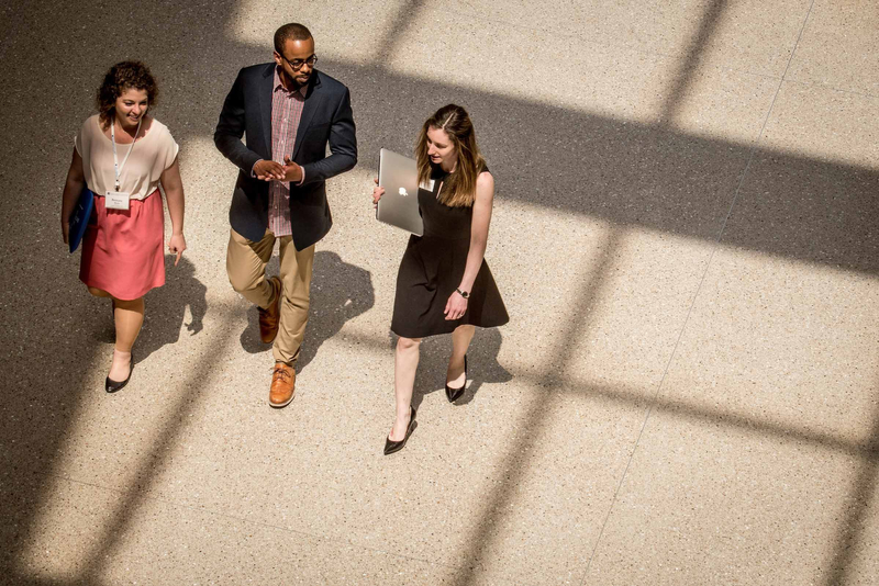 A trio of American University students walking to a campus event underneath a skylight