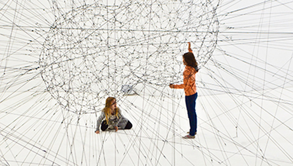 Photographic Representation of AI (Artificial Intelligence) as peanut-shaped web of wires near two young women with crisscrossing wires branching off of center and filling the white room.