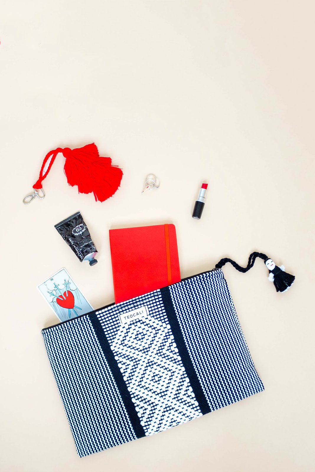 Flatlay of woven bag with lipstick, tarot card, etc, spilling out.