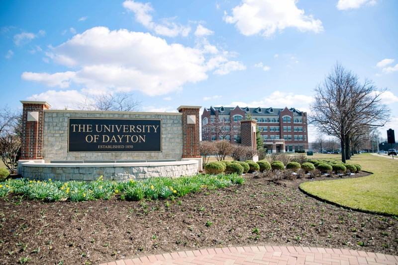 A sign for the University of Dayton in front of a campus building on a sunny day