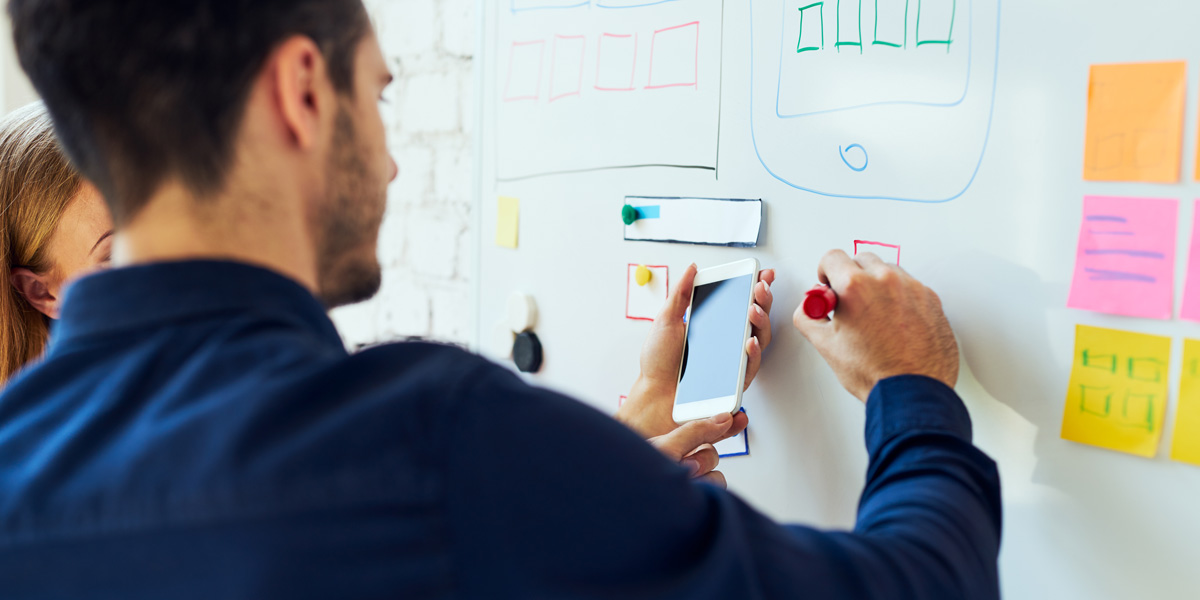 New designers working on a whiteboard prototype