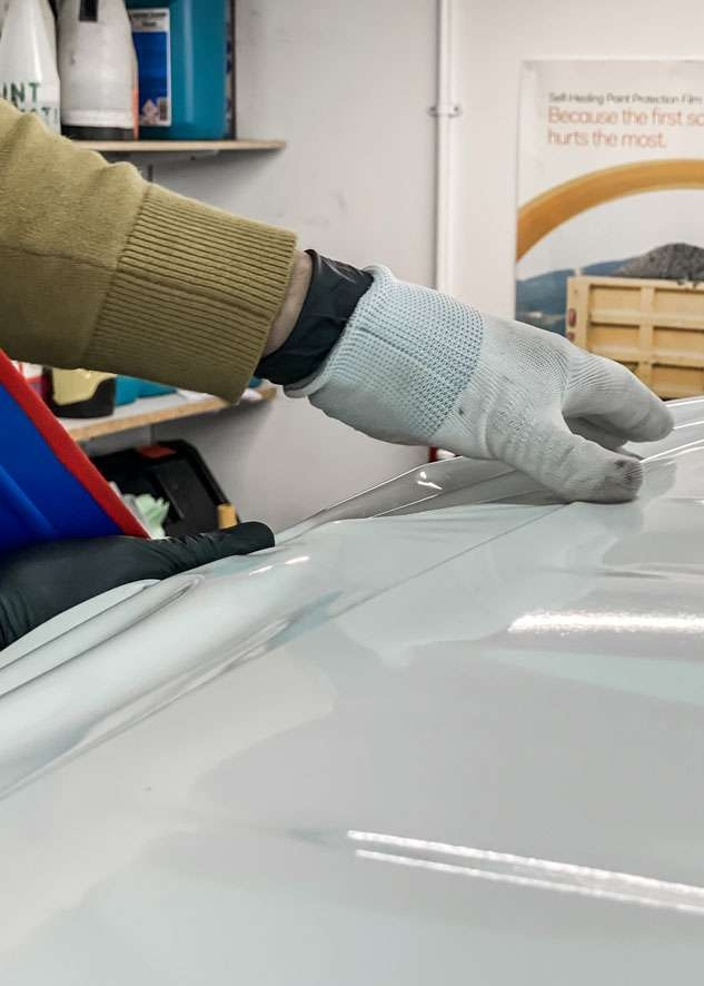 Blue Land Rover Defender roof being vinyl wrapped in white