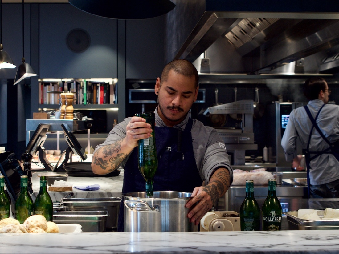 Table Sage's conscious dining values (diversity)- Asian male chef of Amsterdam restaurant Rijk's prepares fine dining dish in Michelin star kitchen