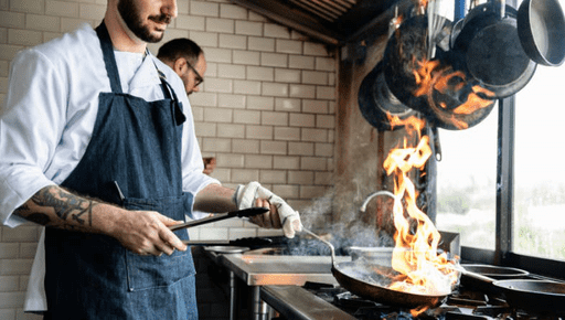 Chef sets pan alight whilst cooking on a stove next to another chef employee in an old kitchen with pots and pants hanging #business