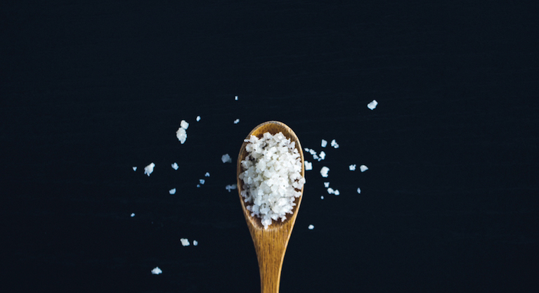 A wooden spoon filled with coarse salt