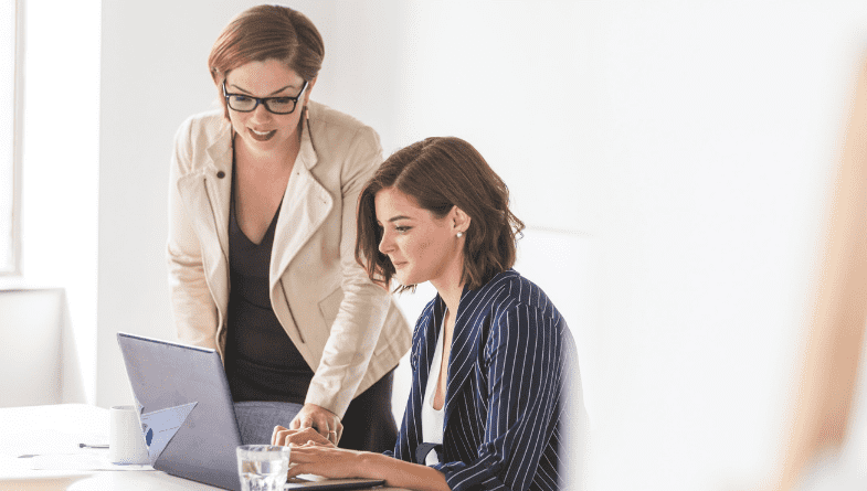 Two women in smart blazers look at a computer screen with financial dashboards, analysing the data in front of a white wall.