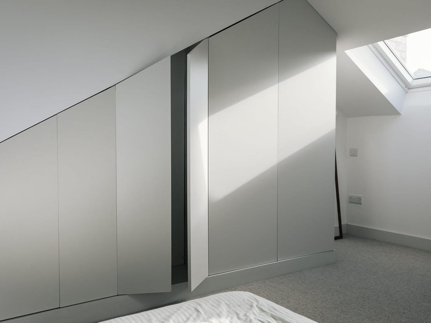 Interior view of built in joinery within the white and grey light filled bedroom in From Works loft conversion and rear dormer extension in Walkley, Sheffield.