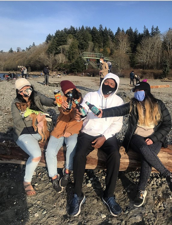Lexi Baasch and her friends pose for a photo together on a log with Pyramid beer while wearing face masks. Water and a forest is in the background.