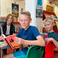 Two boys with books and a Summer Reading Challenge volunteer