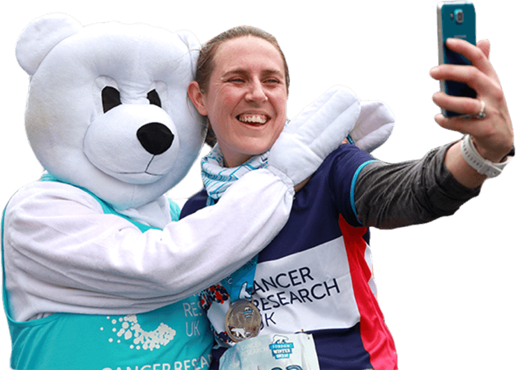 A runner taking a selfie with a polar bear mascot