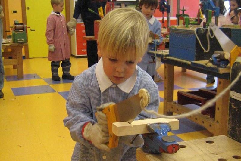 bambino biondo col grambiule che usa la sega per tagliare un legno