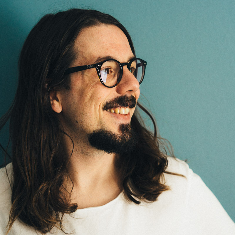 Portrait of a smiling, bearded, and long-haired man wearing glasses.