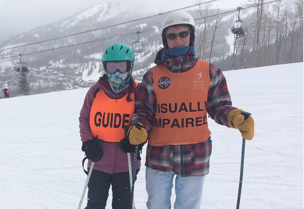 Louie McGee on ski hill standing next to ski guide for visually impaired