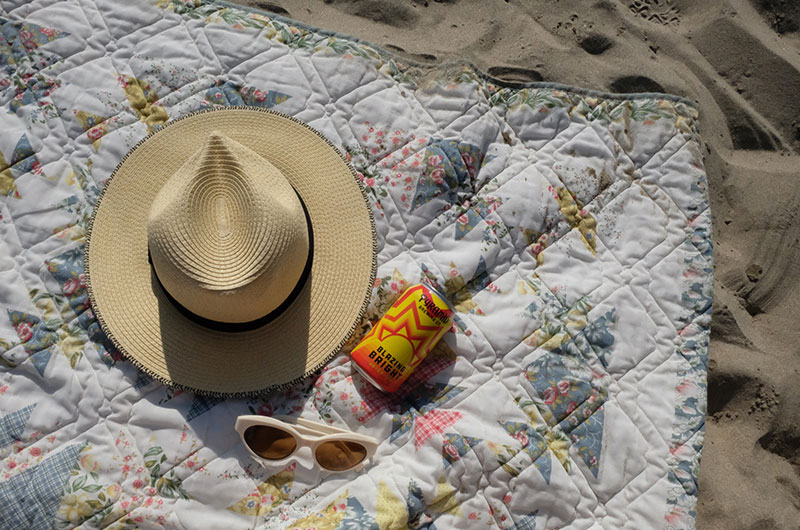A straw hat, sunglasses, and a can of Blazing Bright on a quilted blanket on the sand