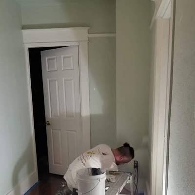 man painting the interior wall of a home