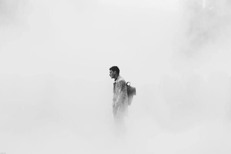 Uma foto em branco e preto de um homem no meio de uma neblina.