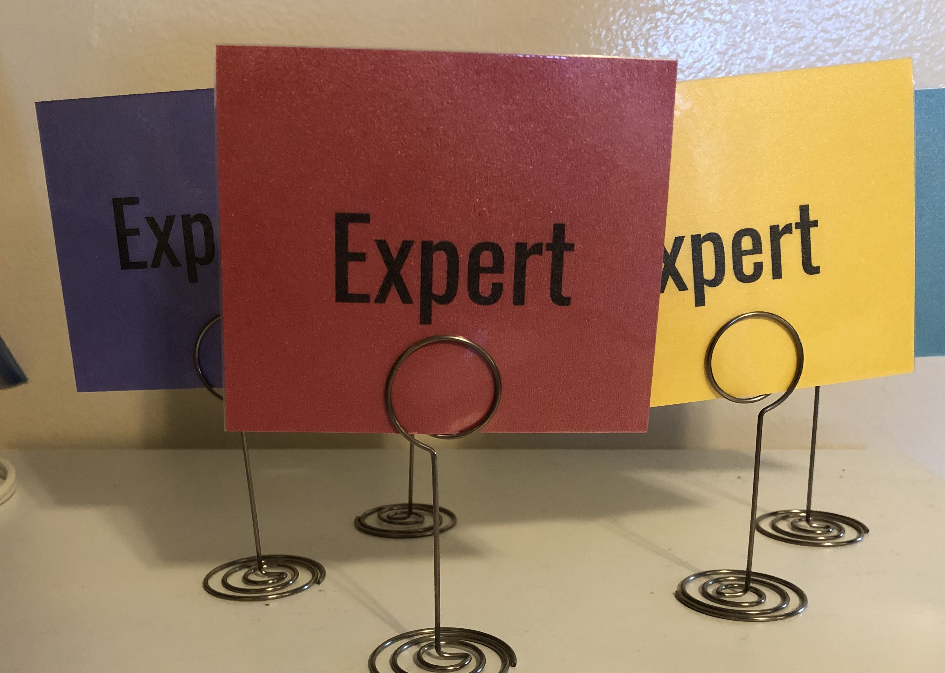 """Card stock cards in multiple colors labeled """"expert"""" and held up by table number holders"""
