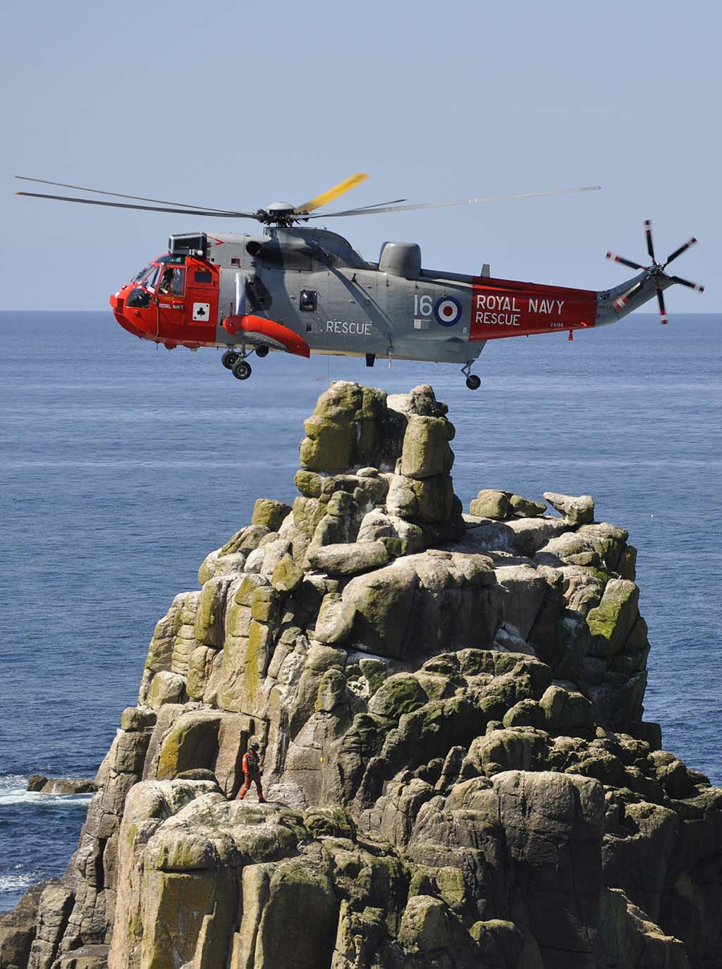 Royal Navy helicopter hovering close to land