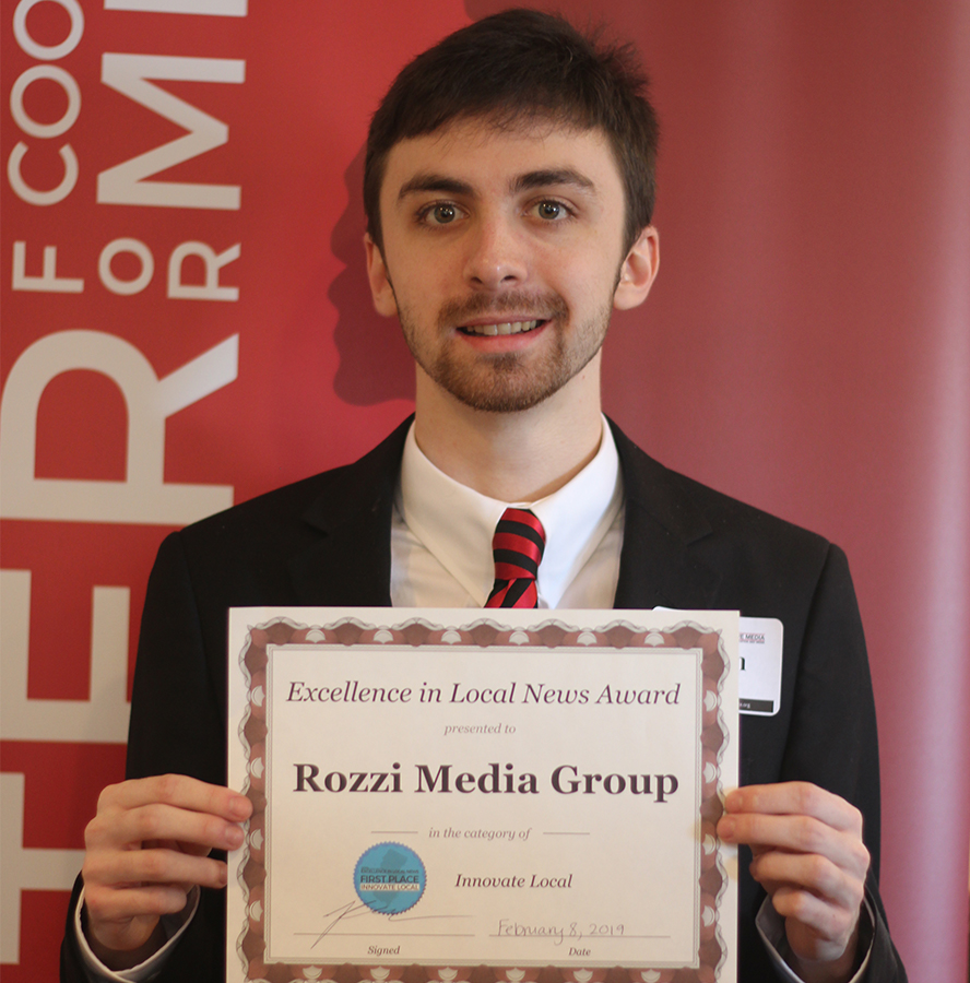 Gavin Rozzi, holding the Excellence in Local News Award