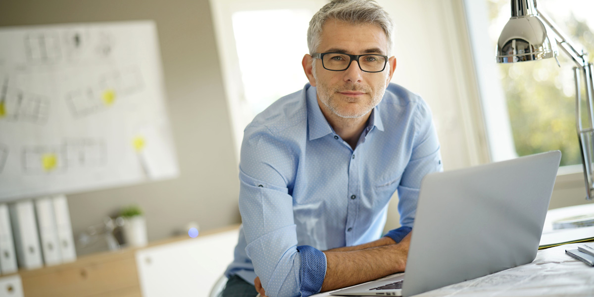 A User Interface Designer smiling slightly, sitting in front of his laptop
