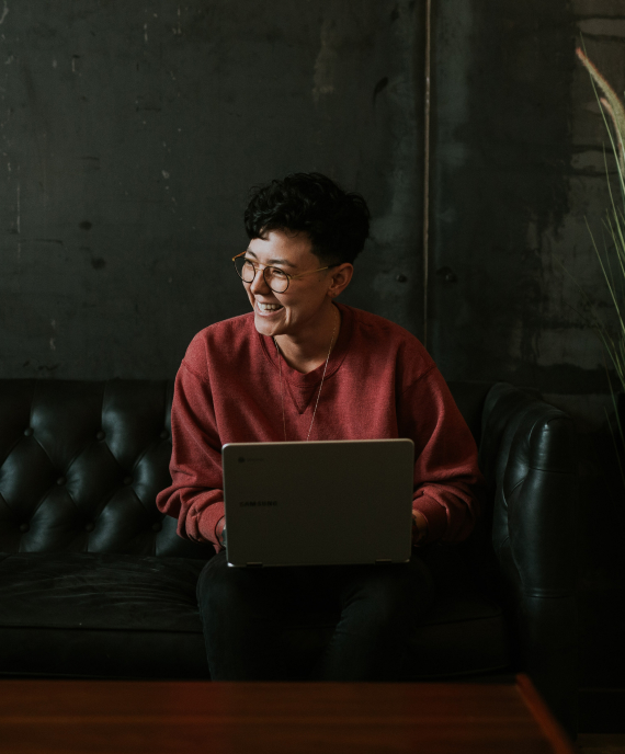 Woman with laptop smiling and looking to her right