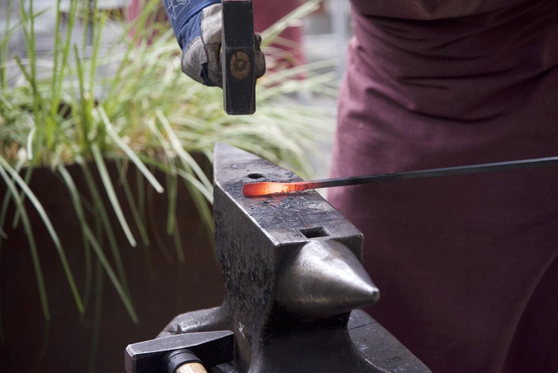 Auf einem Amboss liegt ein heisses Eisen, welches mit einem Hammer bearbeitet wird.
